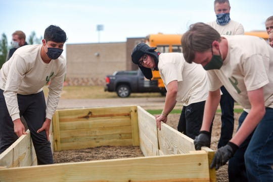 Students Dylan Bonnema, Adam McQuade and Ryan Almquist set wooden planks as they build garden boxes with Ground Works and SD Agriculture in the Classroom on Tuesday, September 29, on the Sioux Falls Christian school campus.