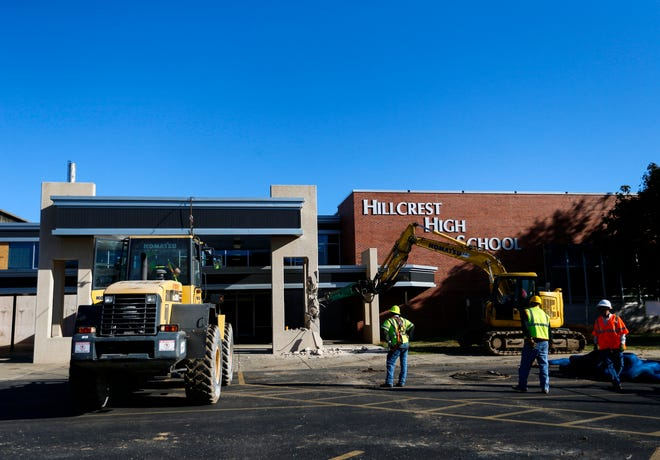 A construction crew using a trackhoe equipped with a jackhammer breaks apart a concrete pillar holding up an awning at Hillcrest High School on Tuesday, Sept. 29, 2020.