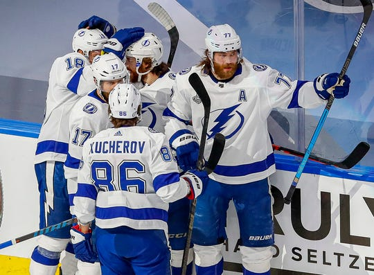 Tampa Bay Lightning players congratulate Brayden Point (21) for his first-period goal.