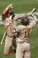 Fernando Tatis Jr. celebrates with Manny Machado after hitting a two-run home run.