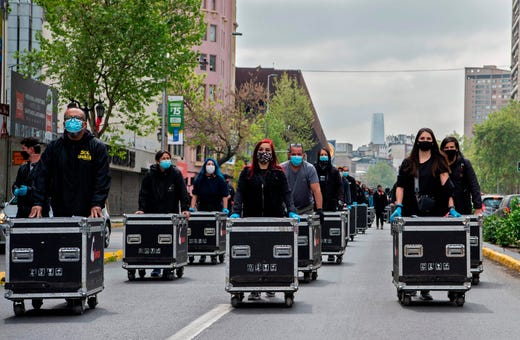 Members of the Arts and Shows Association Union (AGTAE) march pushing boxes with lights and wires during a protest demanding the government of Chilean President Sebastian Pinera for support since they have been inactive for months due to the new coronavirus pandemic, in Santiago on Sept. 29, 2020.