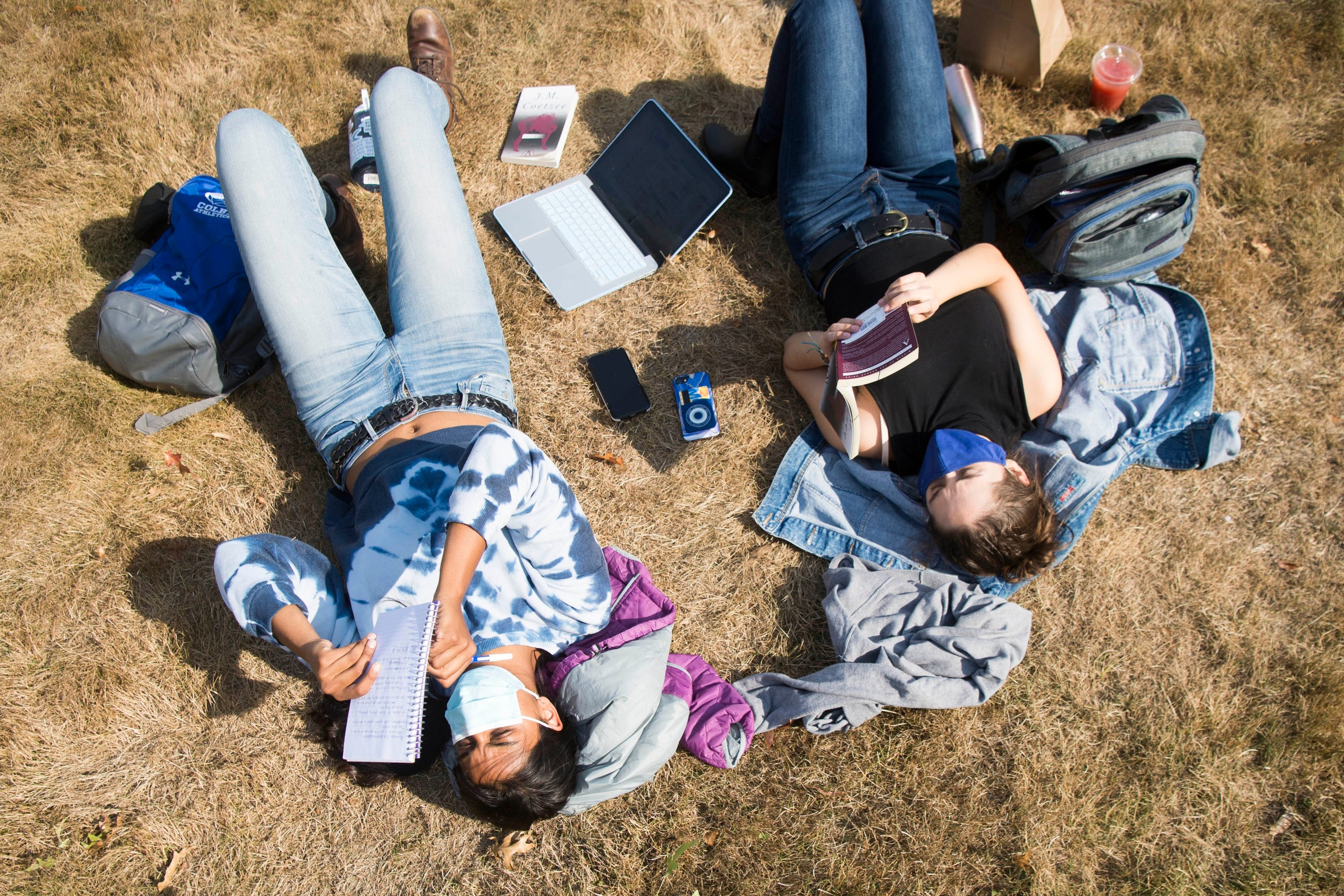Colby College sophomore Mahika Gupta, 19, left, and junior Annie Sternberg, 20, soak up some rays on campus.