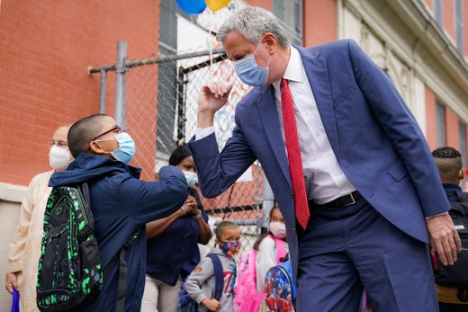 New York Mayor Bill de Blasio, right, greets students as they arrive for in-person classes outside Public School 188 The Island School, Tuesday, Sept. 29, 2020, in the Manhattan borough of New York. Hundreds of thousands of elementary school students are heading back to classrooms starting Tuesday as New York City enters a high-stakes phase of resuming in-person learning during the coronavirus pandemic.