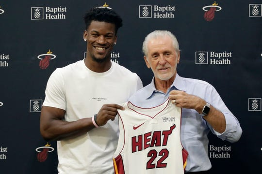 Miami Heat guard Jimmy Butler, left, holds his new jersey as he stands with Miami Heat president Pat Riley on Sept. 27, 2019, in Miami.