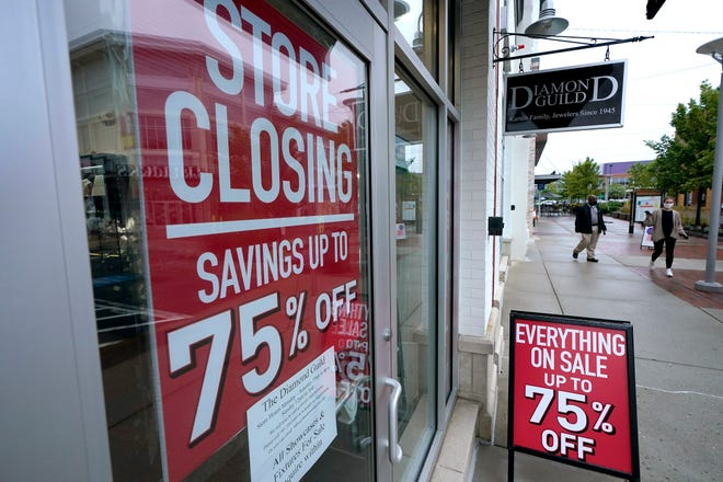 In this Sept. 2, 2020 file photo, pedestrians walk past a business storefront with store closing and sale signs in Dedham, Mass.  The U.S. economy plunged at a record rate in the spring but is poised to break a record for an increase in the just-ending July-September quarter. The Commerce Department reported Wednesday, Sept. 30, that the gross domestic product, the economy's total output of goods and services, fell at a rate of 31.4% in the April-June quarter, only slightly changed from the 31.7% drop estimated one month ago.