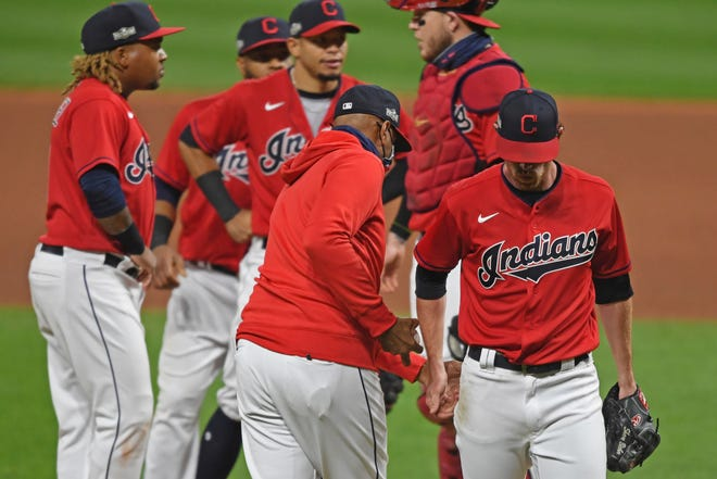 Cleveland Indians starting pitcher Shane Bieber (57) is removed from the game by acting manager Sandy Alomar Jr., center, in the fifth inning of Game 1 of an American League wild-card baseball series against the New York Yankees, Tuesday, Sept. 29, 2020, in Cleveland. (AP Photo/David Dermer)