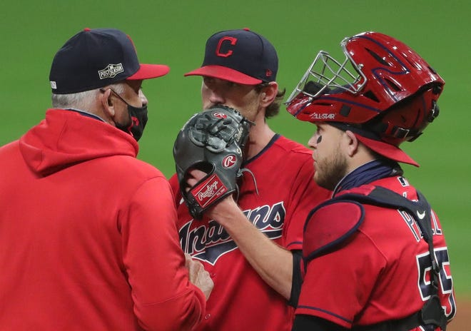Cleveland starting pitcher Shane Bieber has a meeting on the mound with interim manager Sandy Alomar Jr. and catcher Roberto Perez during the playoffs last season. Bieber hopes to have meetings with the team about a contract extension after his Cy Young Award 2020 season. [Jeff Lange/Beacon Journal]