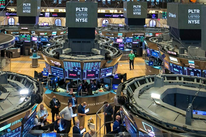 In this photo provided by the New York Stock Exchange, traders, foreground center,  gather at a post on the NYSE trading floor during the direct listing of Palantir Technologies, Wednesday, Sept. 30, 2020. Shares of data-mining company Palantir jumped 47% to $10.67 on their first day of trading. The company was born 17 years ago with the help of CIA seed money. Palantir isn't selling new shares to raise money. Instead, it's listing existing shares for public trading.