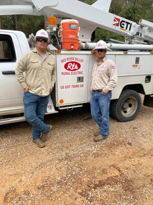Enrique Arguello (left) and Bryce Bumpass (right) stand by a work truck while assisting with restoration efforts in Louisiana. The two linemen visited the state to help repair electric infrastructure following a destructive hurricane.