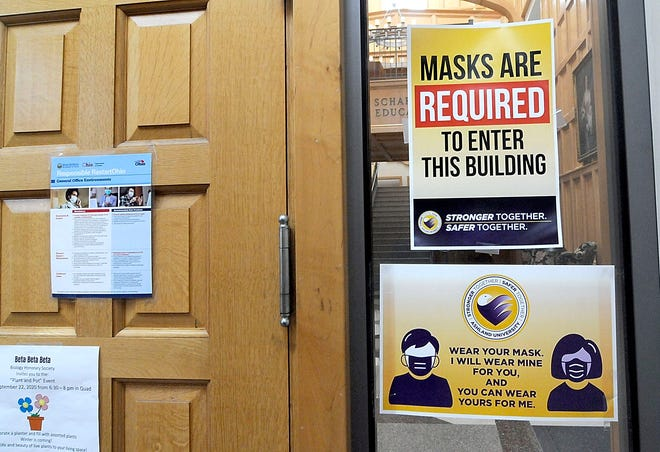 Signs reminding people that masks are required are posted on the entry doors of the Dwight Schar College of Education on the campus of Ashland University on Wednesday, Sept. 30.