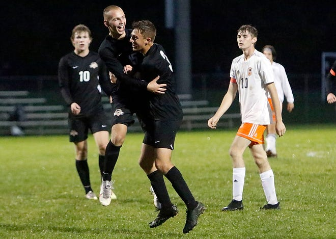 Ashland High's Roman Ramirez (3) is congratulated by teammate Owen Sharick after Ramirez's first half goal during high school boys soccer action against Mount Vernon on Tuesday at Ashland Community Soccer Stadium. Ramirez scored twice in the Arrows' 3-2 victory.