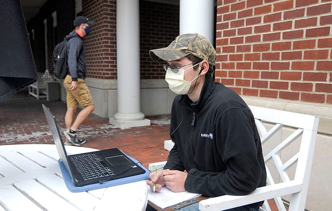 A masked Ashland University freshman, Nikolai Lesnikov, works on an assignment outdoors in September. Ashland County is reporting 631 cumulative cases with 393 presumed recovered, 57 hospitalizations, and 20 deaths.