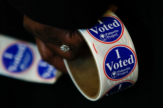 A worker holds stickers at a polling place for the South Carolina primary election Feb. 29 in Columbia.