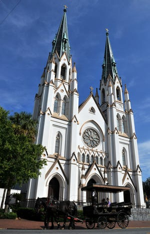 A carriage tour trots along Abercorn Street past the Cathedral of St. John the Baptist.