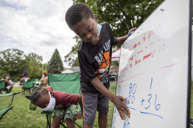 """She'rod Ingram, 6, watches as Javaughn Ingram, 10, works through a math problem as they study together at Driving Park. They were being helped by the Rev. Frederick LaMarr. """"You get them involved at a young age to empower them,""""LaMarrsaid."""