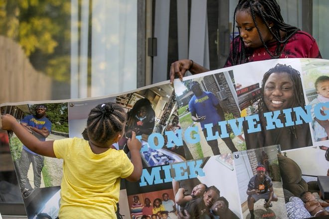 Sabitarry Brice shows off a poster with pictures of her brother, Miekharry Brice, who was killed this year. Miekharry had just learned that his fiancee was expecting his fourth child when he died in August, his sister said.