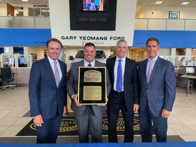 GARY YEOMANS FORD LINCOLN WINS AWARD: Gary Yeomans, left, owner, and Jeromie Allan (holding the award), general manager of Gary Yeomans Ford Lincoln, were recently presented with the President's Award for being one of the top Lincoln dealers in nation in terms of customer satisfaction.