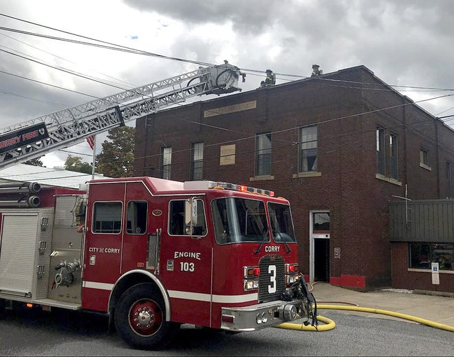 City of Corry firefighters douse a fire on the roof of their fire station at 14 E. South St. after winds blew over a radio tower on the roof and it landed on a live power line on Sept. 30, 2020.
