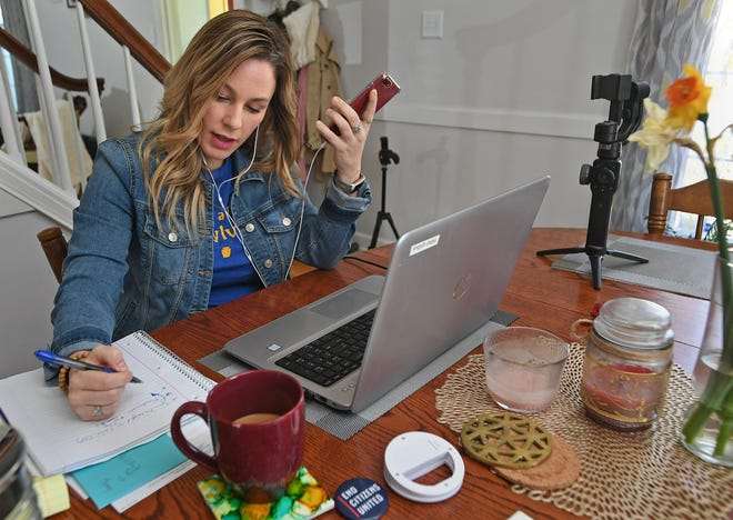 Democratic nominee Kristy Gnibus makes a phone call, takes notes and talks with her campaign team via a Zoom video conference at her home in Millcreek Township in April.