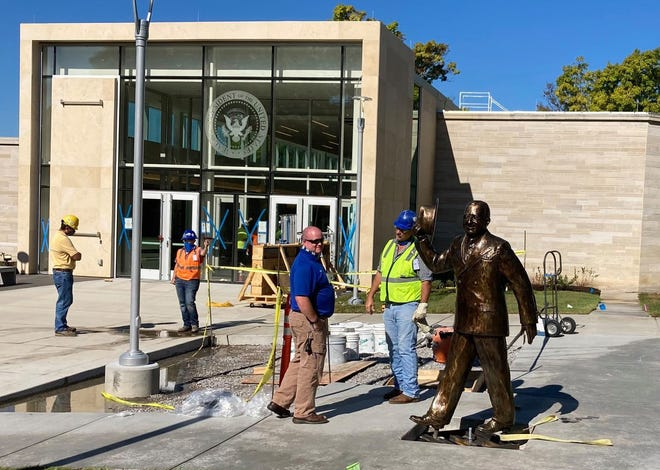 A statue of President Truman waving his hat in greeting stands outside the new entrance of the Truman Library.