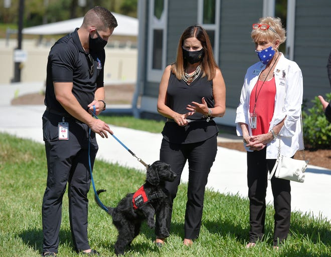 Hayden Reed, the manager of canine support operations at K9s for Warriors, introduces support dog Sully to second lady Karen Pence as she tours the facility with founder Shari Duval Wednesday afternoon.  The visit to K9s for Warriors came between stops at NAS Jacksonville and Social Ground Coffee Co. in Jacksonville's Springfield neighborhood, where she learned about their work supporting veterans.