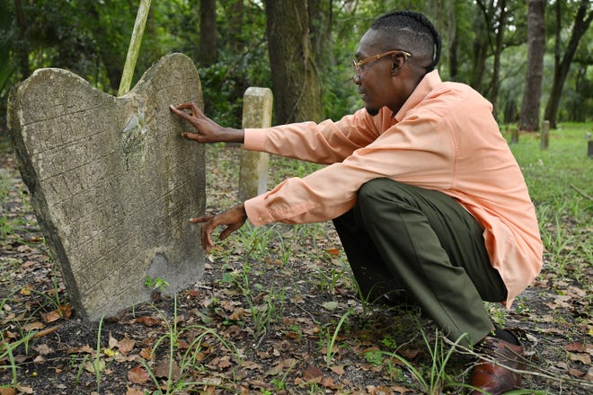 Michael Swain looks at a poured concrete headstone with a date of birth from 1861, which was handwritten in the wet concrete and had a small model of a bird pressed into it. Swain has been documenting and researching many of the gravesites in the long-neglected Greenwood Cemetery off Moncrief Road across from Raines High School.