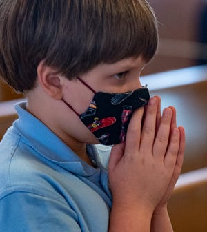 Third grader Silas Allbrook, prays during St. Charles Borromeo School's 100th anniversary Mass, held Wednesday, Sept. 30, 2020.