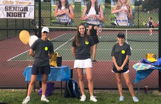 Tallmadge girls tennis seniors, from left, Anna Siesel, Elena Kozma and Claudia Palmer, celebrate during Tallmadge's senior night.