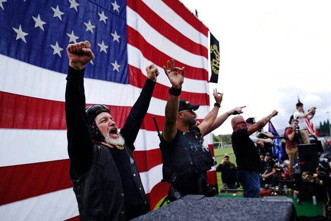 """Members of the Proud Boys cheer on stage as they and other right-wing demonstrators rally, Sept. 26, 2020, in Portland, Ore.  President Donald Trump didn't condemn white supremacist groups and their role in violence in some American cities this summer. Instead, he said the violence is a """"left-wing"""" problem and he told one far-right extremist group to """"stand back and stand by."""" His comments Tuesday night were in response to debate moderator Chris Wallace asking if he would condemn white supremacists and militia groups. Trump's exchange with Democrat Joe Biden left the extremist group Proud Boys celebrating what some of its members saw as tacit approval."""