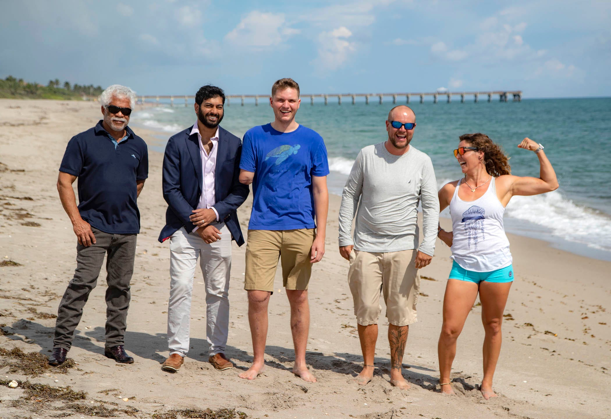 At their 10-month reunion, Dr. Robert Borrego, from left, Dr. Dilhan Abeyewardene, Carter Viss, Andy Earl and Christine Raininger meet on the beach. The doctors from St. Mary's Medical Center saved Viss' legs and repaired his broken hand after the Thanksgiving Day 2019 accident. To get him to the hospital alive, his friend, Earl, kept him afloat while Raininger, a stranger, tied a tourniquet on his severed arm.