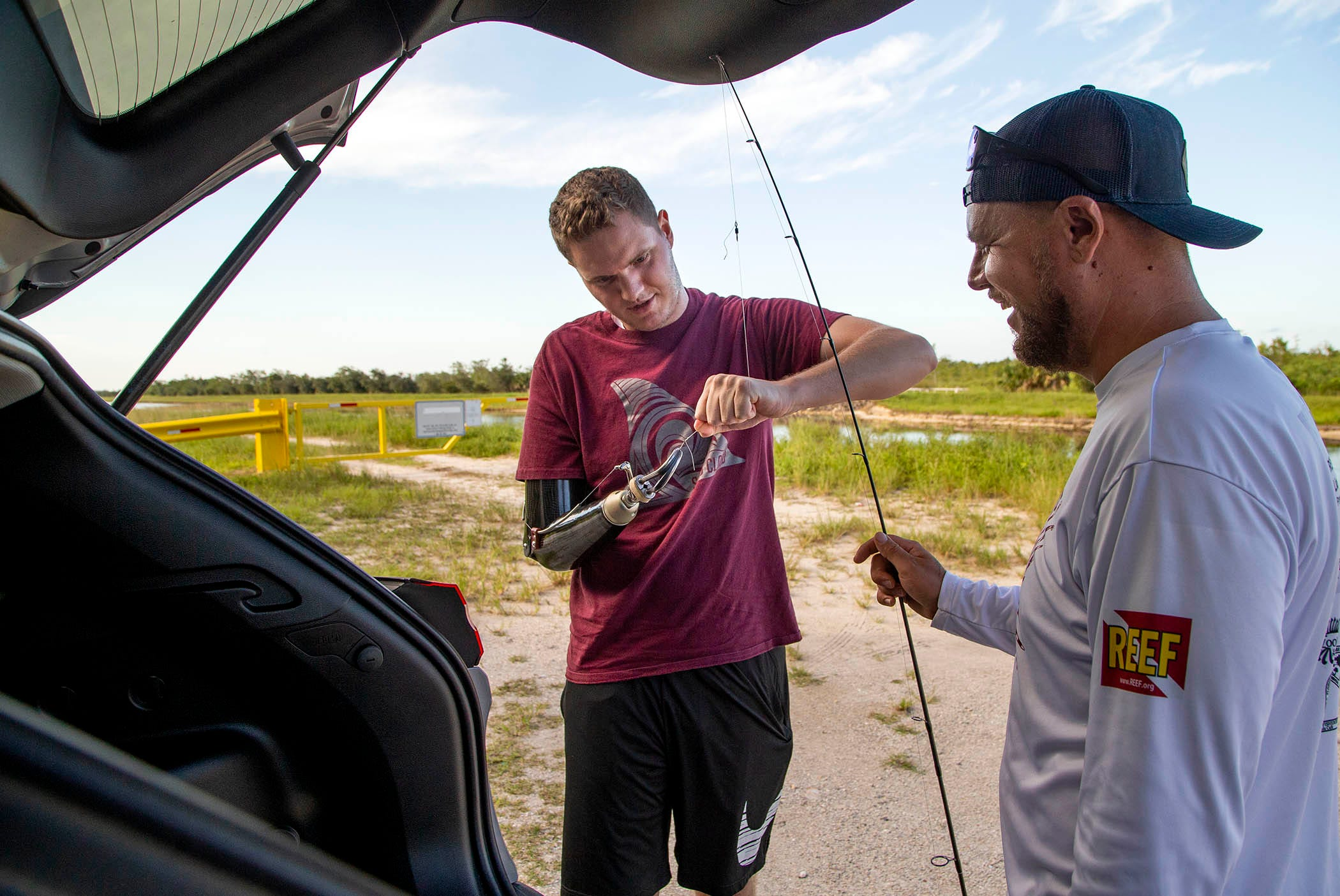 Carter Viss ties a knot in his fishing line on Aug. 7 as he prepares to go fishing at Sandhill Crane Access Park with his friend and rescuer Andy Earl.