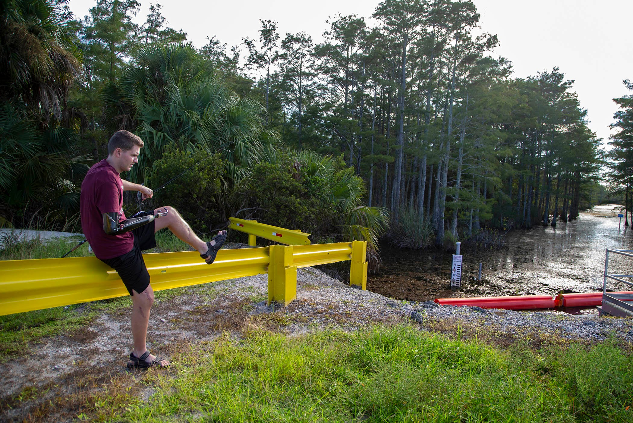 Carter Viss hops over a guardrail on Aug. 7 while fishing at Sandhill Crane Access Park in Palm Beach Gardens.