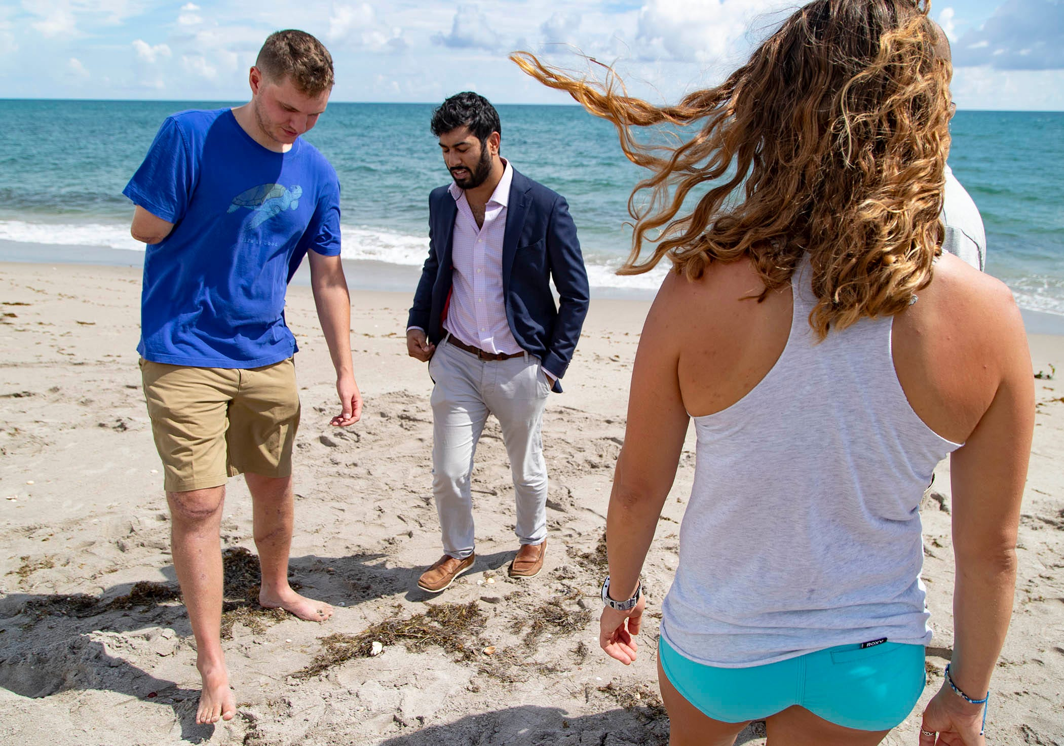 Carter Viss, the marine biologist who lost his arm when he was hit by a boat in the ocean while snorkeling last Thanksgiving Day, talks with orthopedic surgeon Dr. Dilhan Abeyewardene, who helped save Viss' legs after the accident. Viss reunited with some of the people who saved his life 10 months ago including Christine Raininger, right, who came to his rescue in the sea.