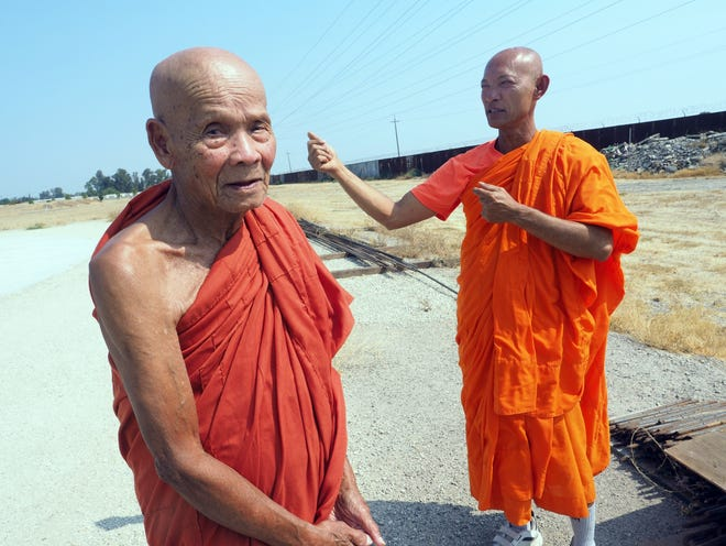 Head Monk Kuch Pum, left, and Senior Monk Kong Tith near the foundation for the towering Heaven structure at south Stockton's Wat Dhammararam Buddhist Temple. Temple officials have had to scale back construction on the structure because of the pandemic.
