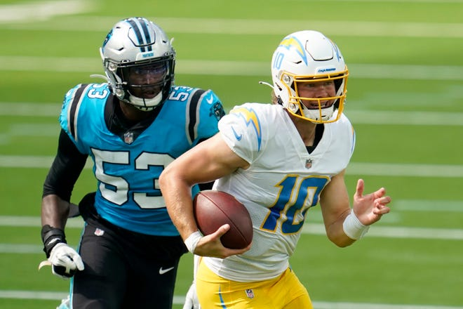 Los Angeles Chargers quarterback Justin Herbert (10) scrambles away from Carolina Panthers defensive end Brian Burns during the second half of Sunday's game in Inglewood, Calif