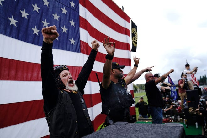 """FILE - Members of the Proud Boys cheer on stage as they and other right-wing demonstrators rally, Saturday, Sept. 26, 2020, in Portland, Ore.  President Donald Trump didn't condemn white supremacist groups and their role in violence in some American cities this summer. Instead, he said the violence is a """"left-wing"""" problem and he told one far-right extremist group to """"stand back and stand by."""" His comments Tuesday night were in response to debate moderator Chris Wallace asking if he would condemn white supremacists and militia groups. Trump's exchange with Democrat Joe Biden left the extremist group Proud Boys celebrating what some of its members saw as tacit approval. (AP Photo/John Locher)"""