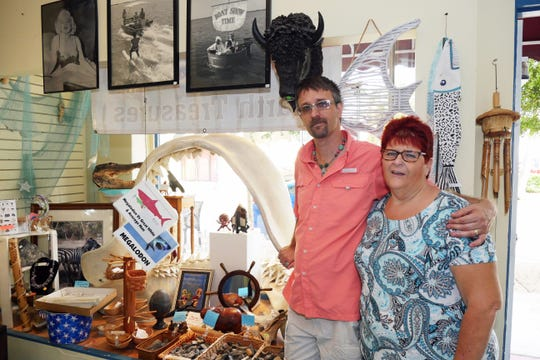 Don and Draeanne Rivette, owners of Earth Treasures on Miami Avenue, pose in front of their display window, which includes a model of the jaws from a 42-foot-long Megalodon shark. Earth Treasures is one of two shops on the island of Venice that offer beachcombers expertise on the hobby of collecting sharks teeth and fossils.