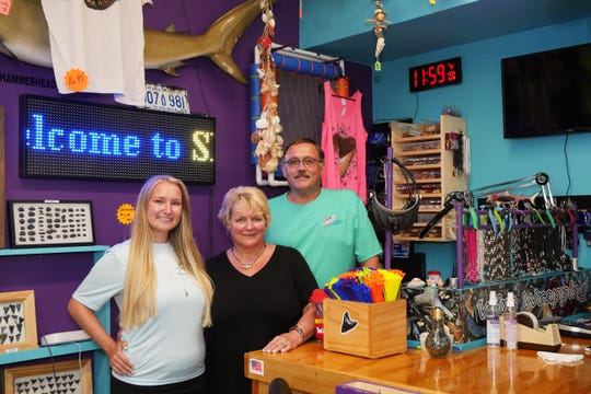 Brittanie Hervas poses with her parents Linda and Roy Hervas behind the counter at Shark Frenzy, the beachcombing store they opened up in December, 2019 on Tamiami Trail.