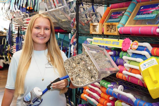 Brittanie Hervas shows off a display model of the Shark Tooth Sifter, a patented tool for scouring the seashore for sharks teeth, shells and fossils that her family designed and sells at Shark Frenzy, a store she opened with her parents Roy and Linda in December, 2019.