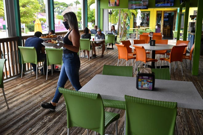 A server waits on customers at the Daiquiri Deck. It's hard for service workers, and many others, to make enough to live in the Sarasota-Manatee area, especially since the pandemic began.