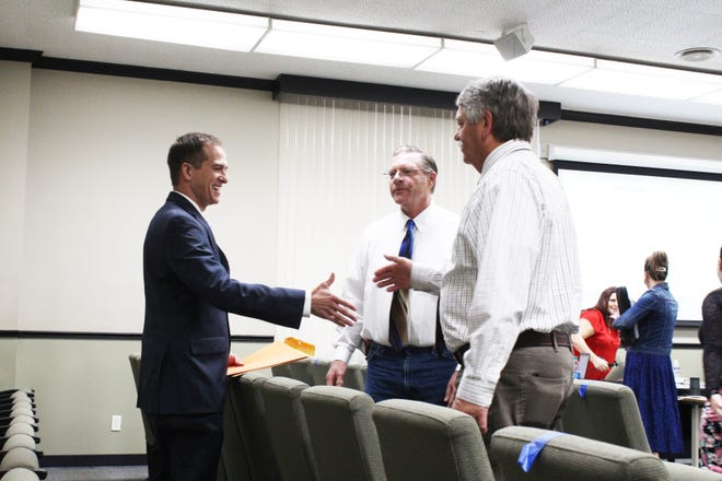 Jeremiah LaRue shakes Siskiyou Supervisor Ray Haupt's hand right after  it was announced that he had been selected to serve as the next Siskiyou County Sheriff at the conclusion of a special Board of Supervisors meeting in Yreka on Sept. 29, 2020. Also pictured is Supervisor Michael Kobseff, center.
