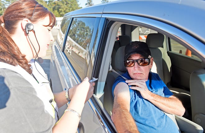 Lindsey Laminack gives a flu shot to David Robertson at the Etowah County Health Department's drive-thru flu shot clinic in the parking lot at North Glencoe Baptist Church in Glencoe in a file photo from 2015.