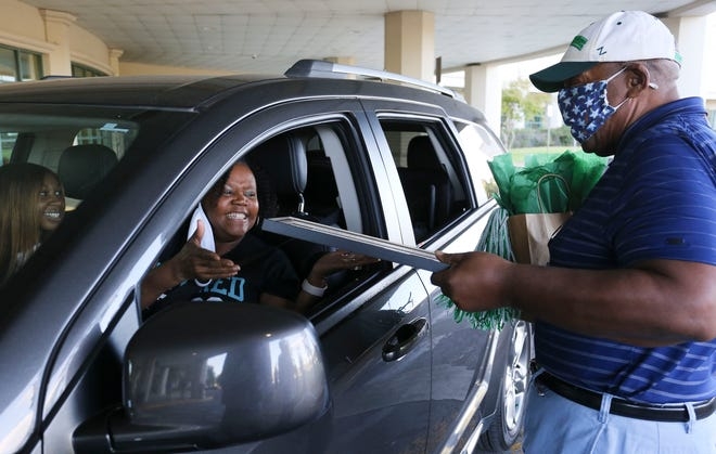 Rodney Landrum presents gifts to Andrea Parker as Shelton State honors retirees with a COVID-19 friendly auto parade through the main campus Tuesday, Sept. 29, 2020. [Staff Photo/Gary Cosby Jr.]