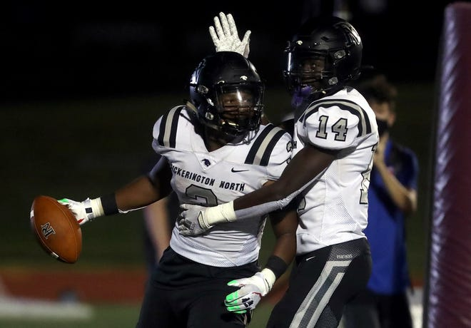 Pickerington North's Dawaun Green (left) and Carl Allen II celebrate Green's 10-yard touchdown run against host New Albany on Sept. 25. The Panthers defeated the Eagles 56-21.