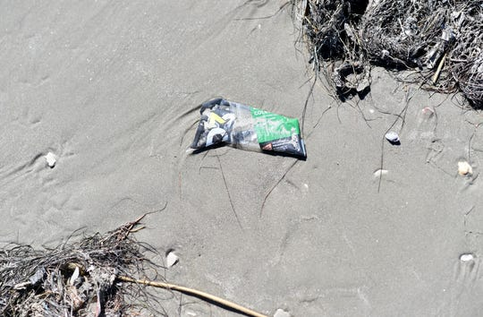 Trash in seen on Michael J Ellis Beach, Tuesday, Sept. 29, 2020. Coffee lovers can collect a bag of beach trash and exchange it for a free cold brew at Island Joe's.