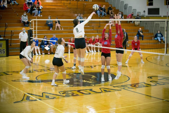 Ashley Newell sends a hard hit ball across the net and over the of two West Holmes blockers during Tuesday night volleyball action at River View High School.