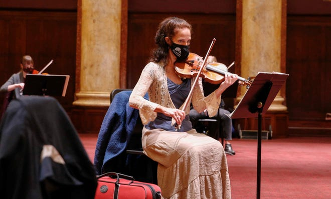 Des Moines Symphony Orchestra violinist Danna Pins warms up prior to rehearsal on Tuesday, Sept. 30, at the Temple for Performing Arts in Des Moines.