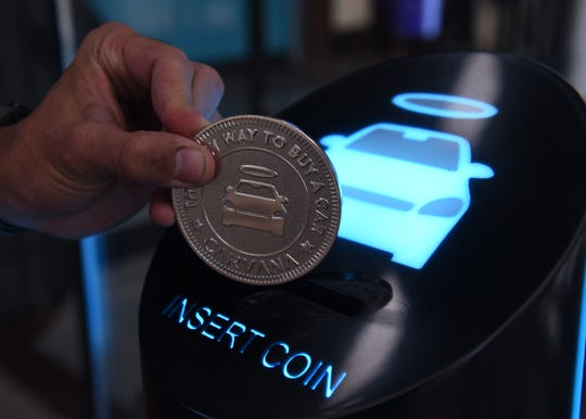 A token is inserted in the Carvana tower to pick up your car after purchase.