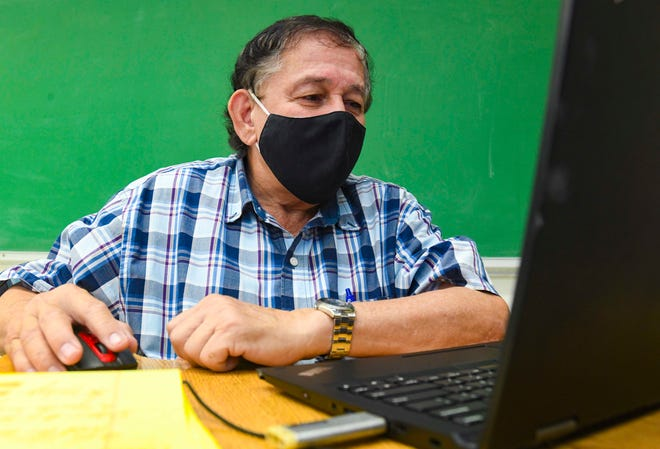 Sixth-grade science teacher Frank Borja sits in an Inarajan Middle School classroom as he interacts with his students online during a virtual classroom lesson in this Sept. 30 file photo. Superintendent Jon Fernandez said face-to-face learning in the public schools doesn't look promising in January, based on the number of COVID-19 cases.