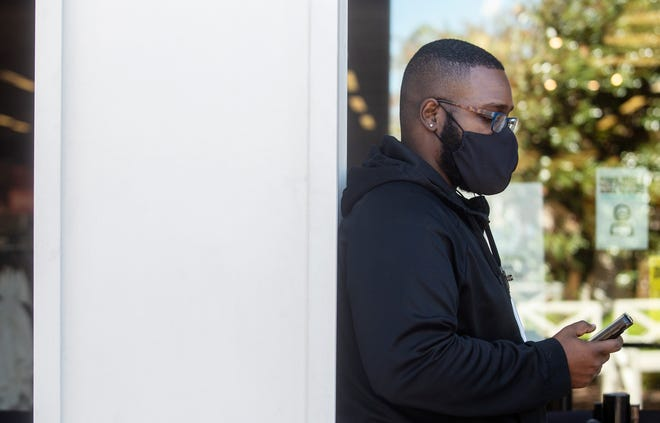 Nike Factory Store employee David Sturgis checks his text messages while wearing a mask at the Outlets of Mississippi in Pearl, Miss. Wednesday, Sept. 30, 2020.